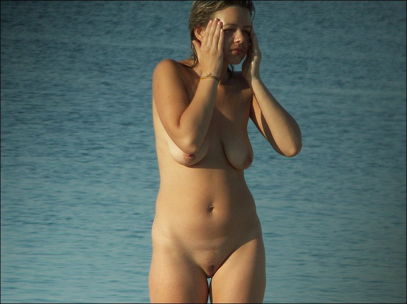 Delicious shaved camel toe revealed on a nudist beach while a naked babe woke up from beauty sleep