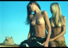 Awesome damsels with long hair and round gorgeous bobbies wearing no bra posing at the beach