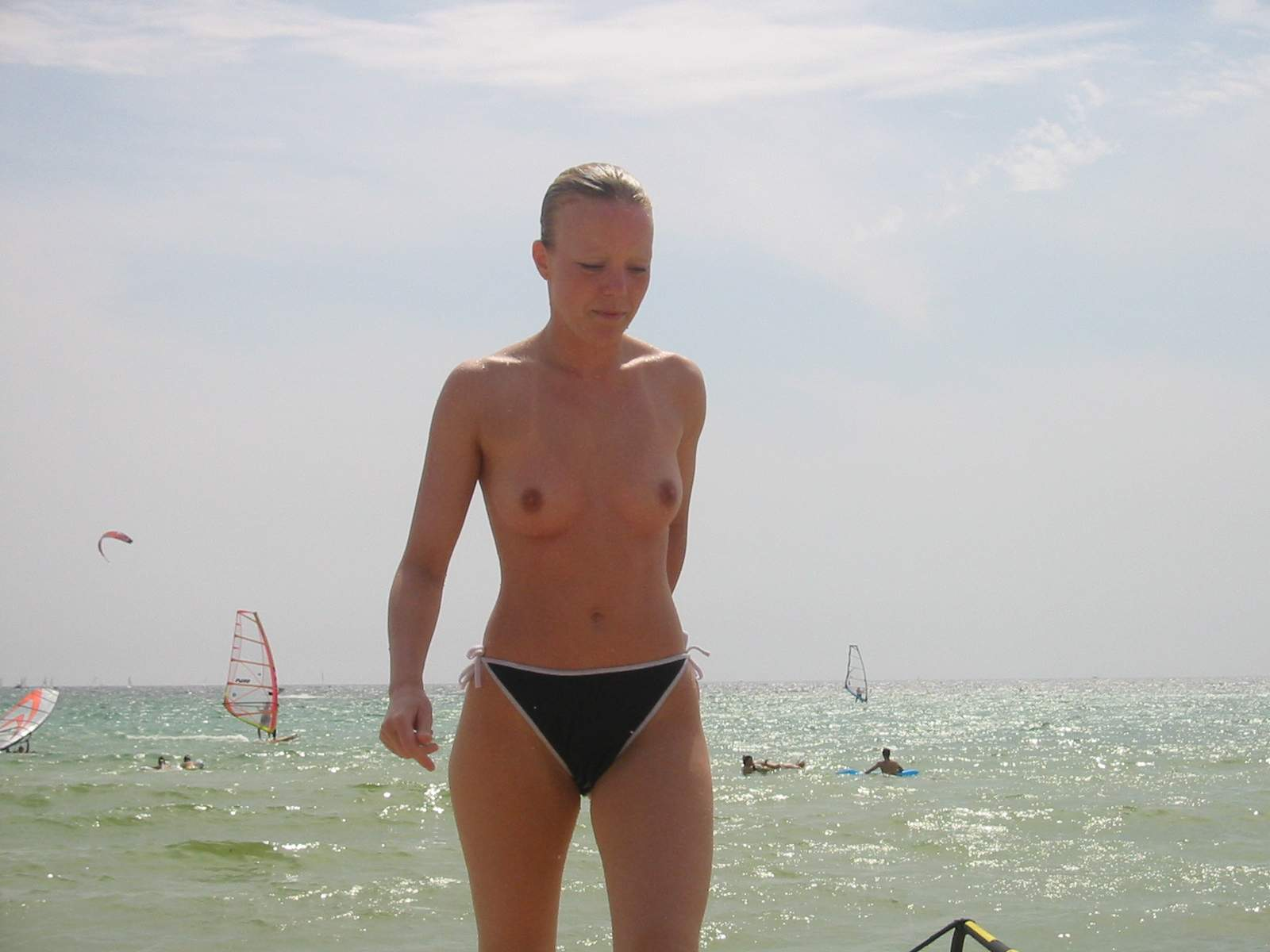 Topless babe caught on a wild beach exposing her wonderful titties and hard brown nips