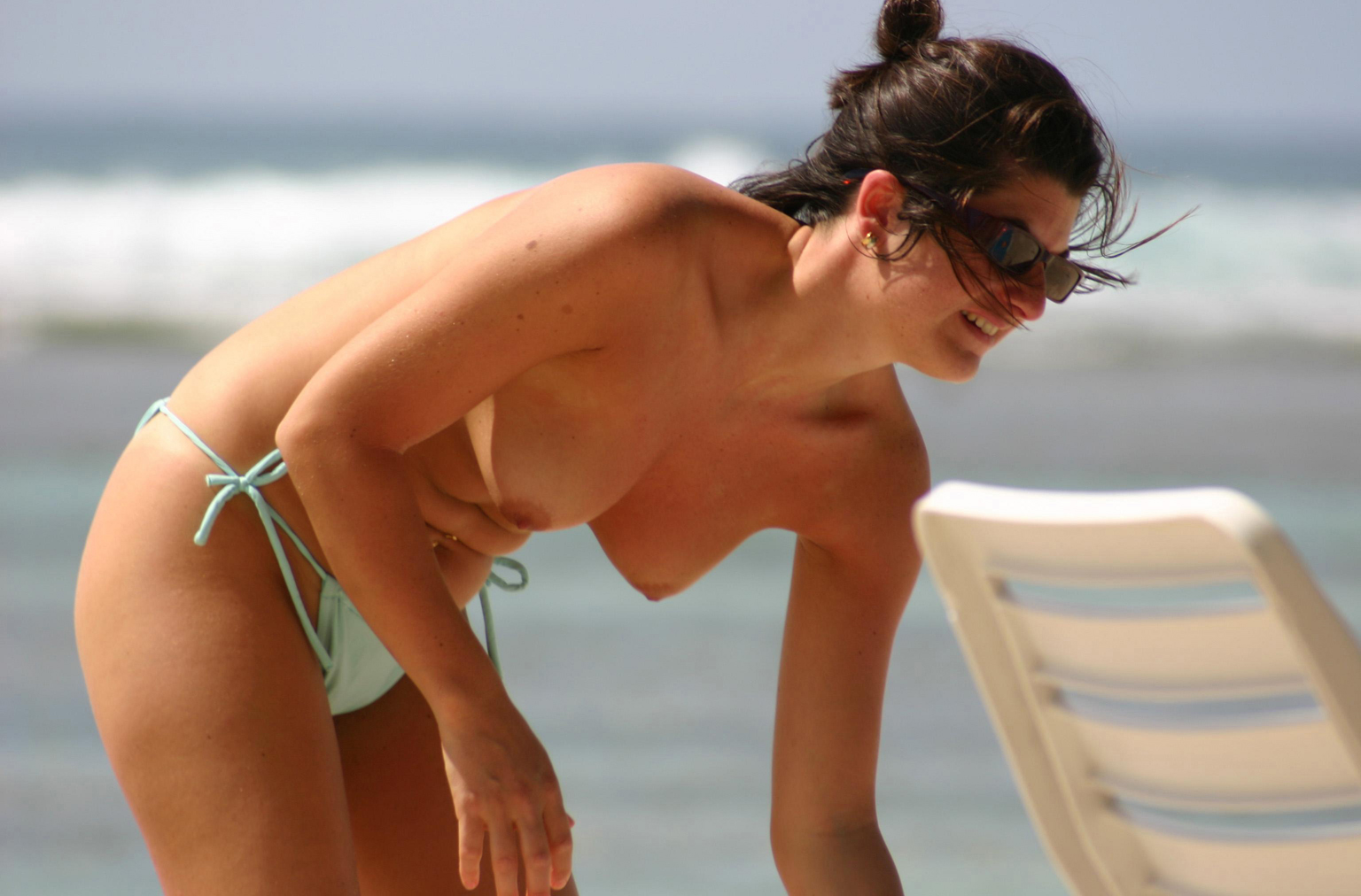 Topless brunette babe caught by a spy on nudist beach with hard pokies and wearing sunglasses