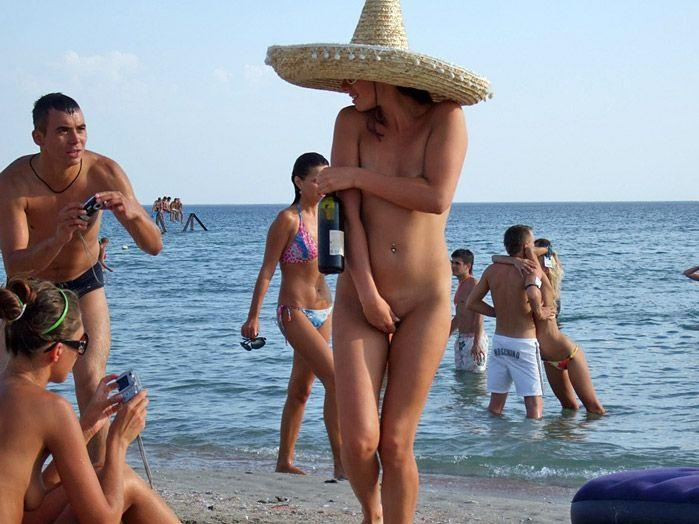 Mexican woman babe at the beach hiding her nudity while from the male photo camera
