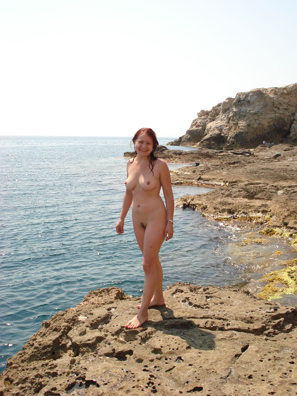 Naughty girl sexy photo shoot on a rocky beach fully nude with her hairy muff