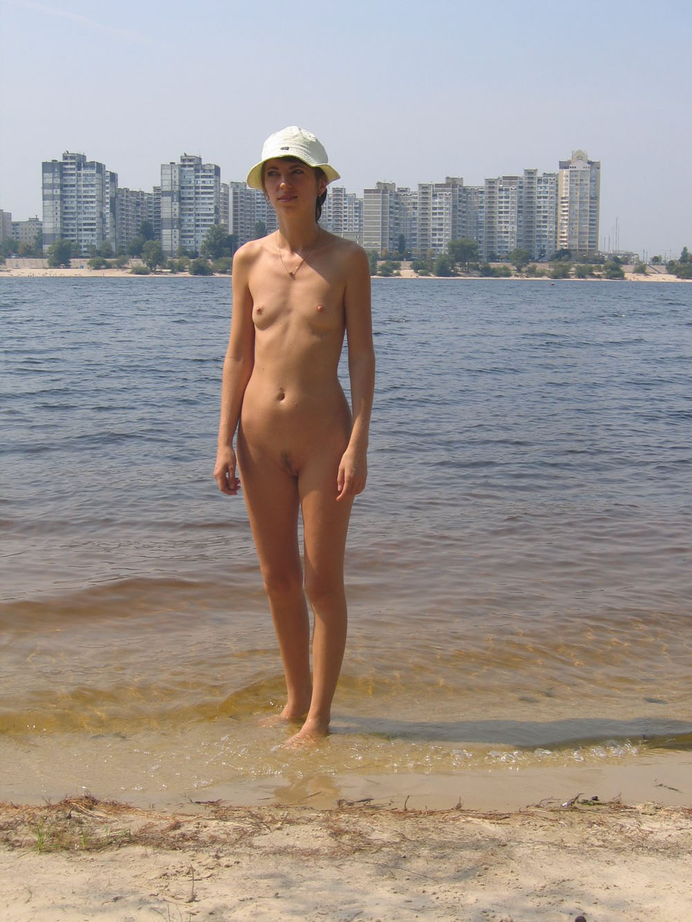 Small tits naked body babe on a nudist beach show her furry pussy stripe and excited pokies