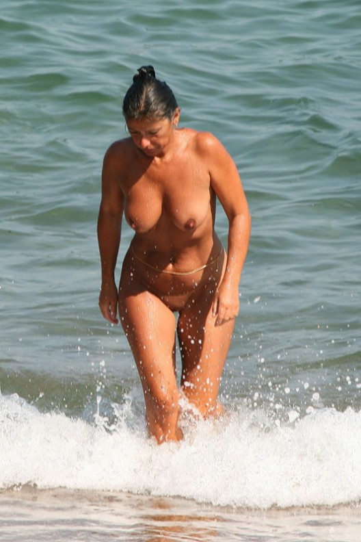 Shaggy nude female well tanned exit from the ocean water to expose excited nips and fantastic pussy