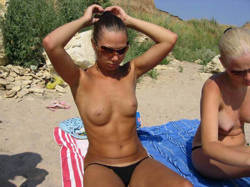 Wicked tanned goddess ties her hair in a secure bun