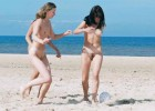 Attractive nude girls playing soccer in the sand
