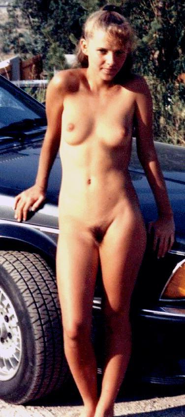 Car presenting naked model showcases bushy muff