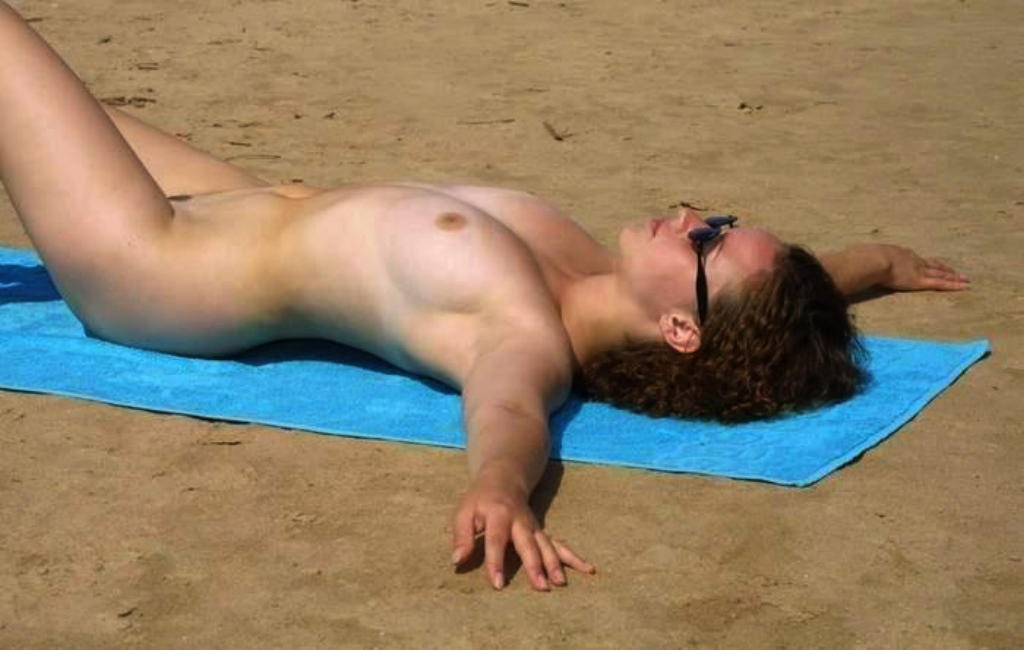Curly haired nudist lays down like a starfish