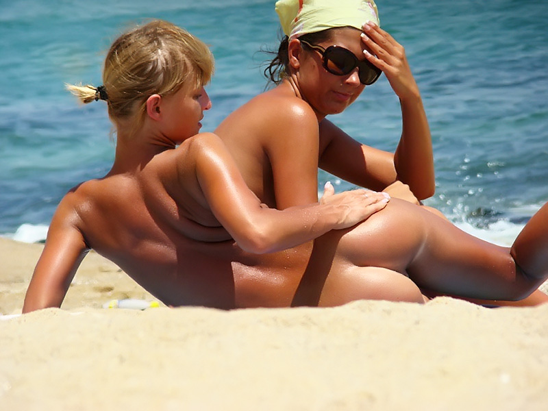 Naked babe feels the tingle of the heat of the sand and checks her ass out while girlfriend watches
