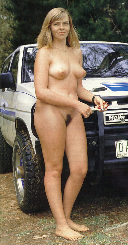 Naked lady poses near her car coming and going bumper to bumper