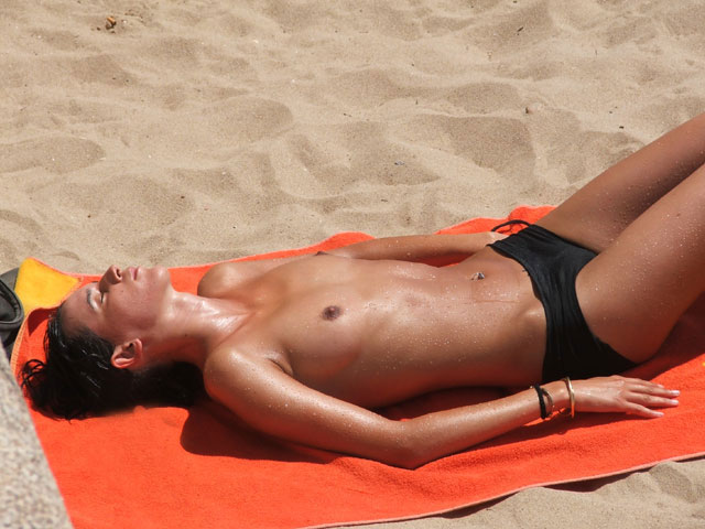 Pretty sunbathing damsel gets splendidly erotic while lying naked in the sand