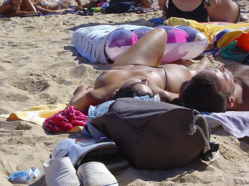 Topless babe canoodling with her boyfriend at the beach