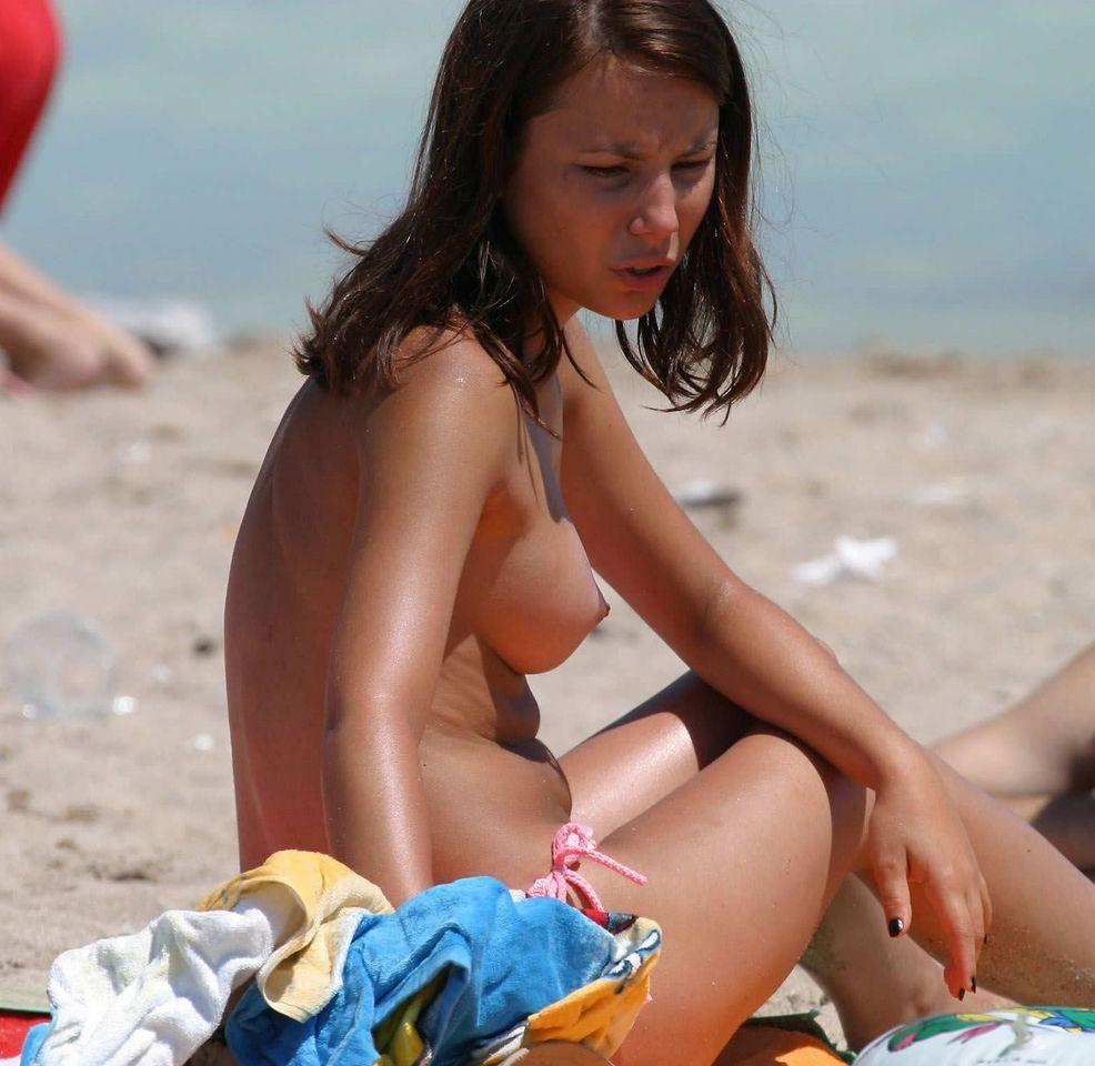 Beach attendant rubs suntan oil on angelys 6