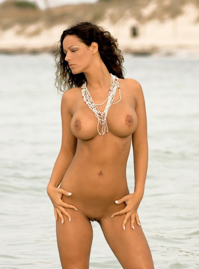 Check out this smoking hot brunette naked at the beach