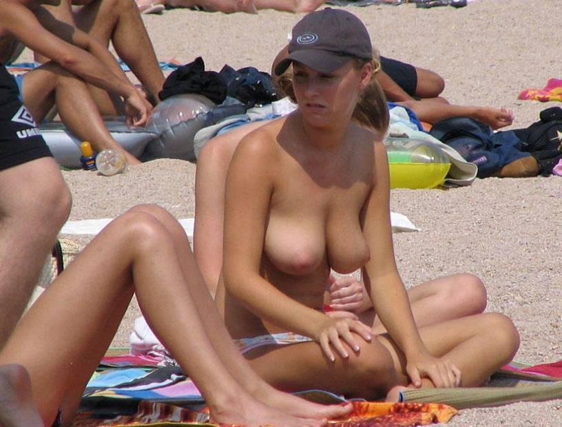 Pretty topless maiden unwary of lurking beach voyeurs