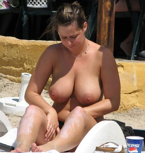 This hot brunette babe has enormous tits and some suncream