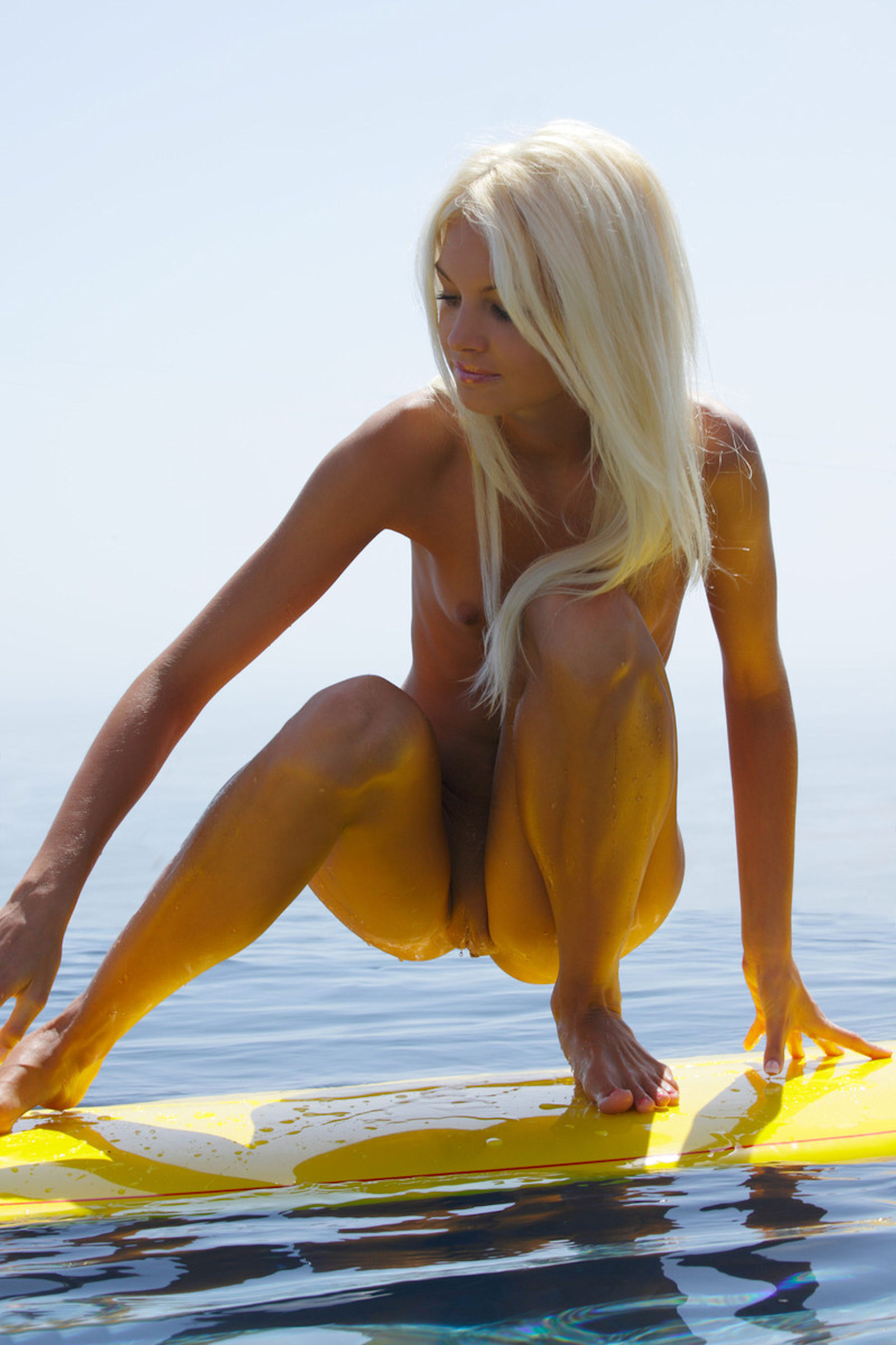 Beauty squatting on the surfboard completely naked