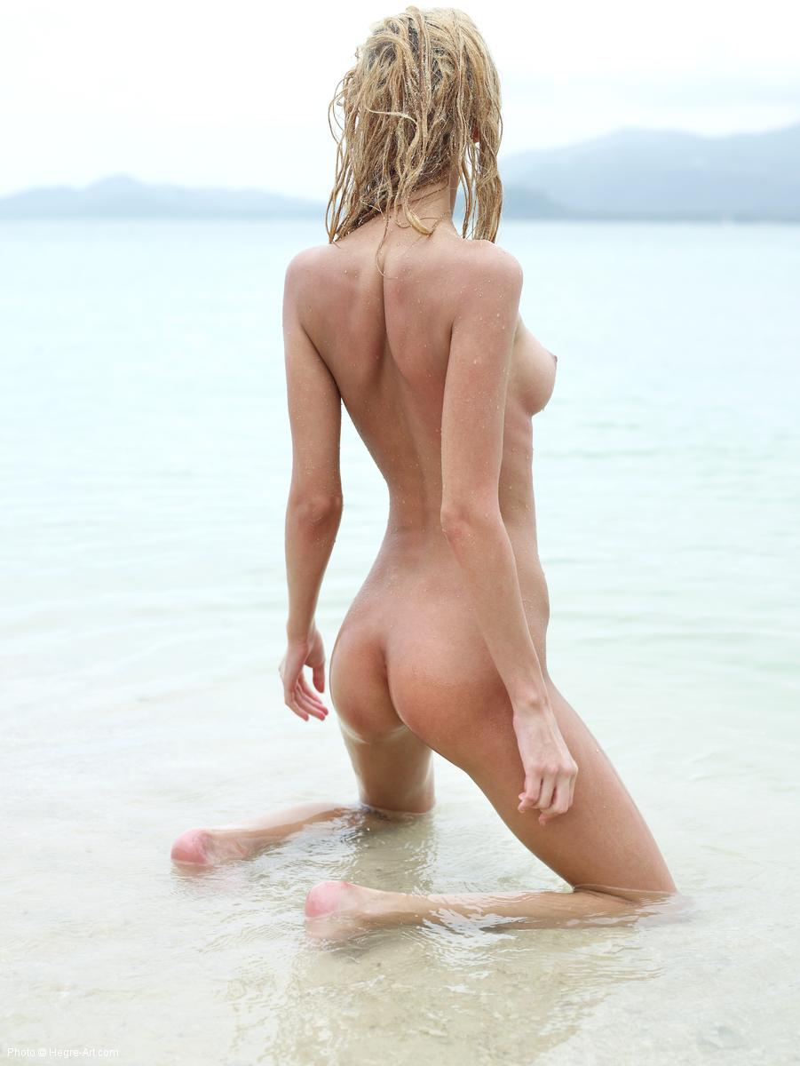 Naked babe kneeling in the sea