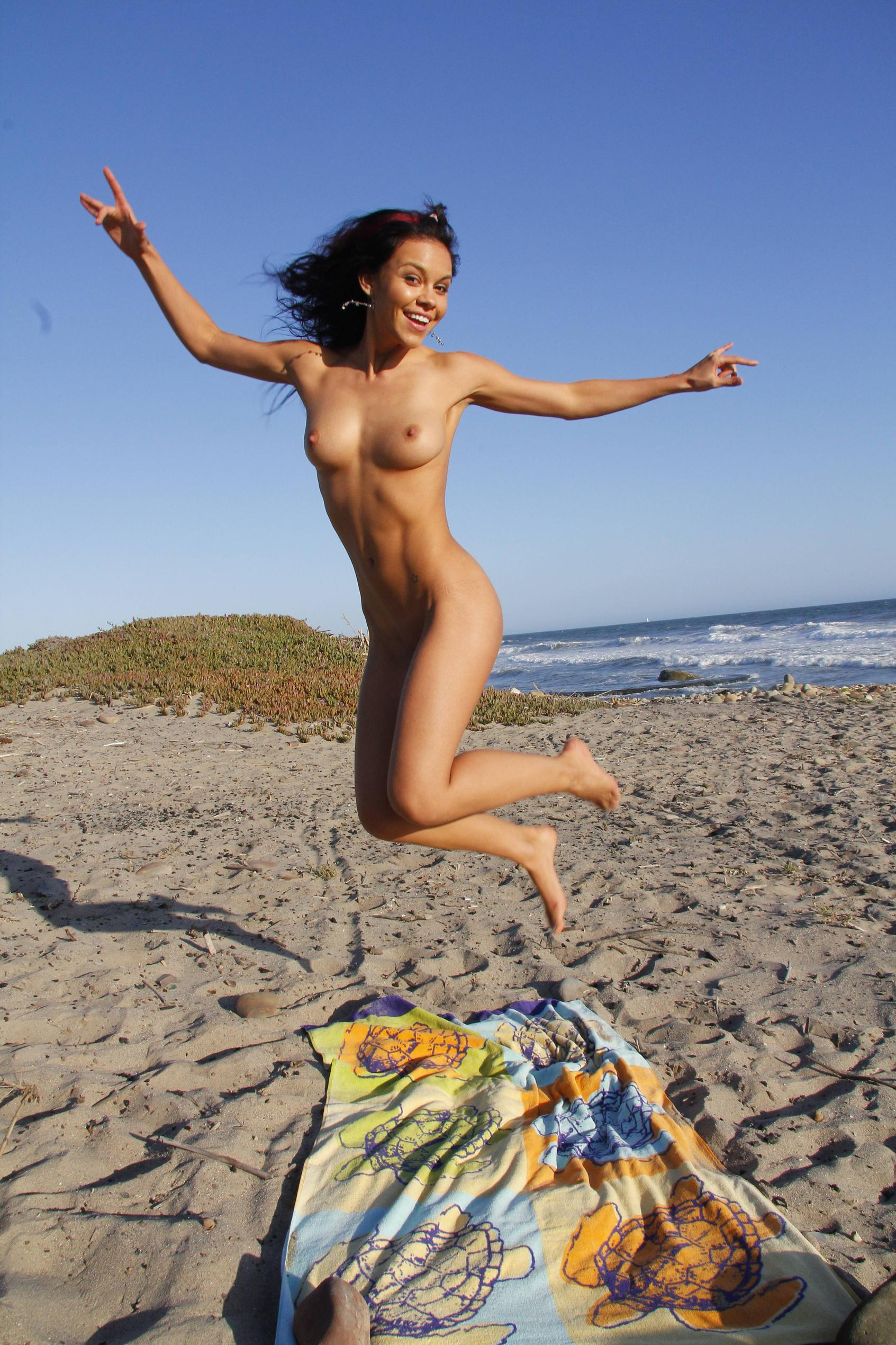 Playful hot girl jumping naked on the beach