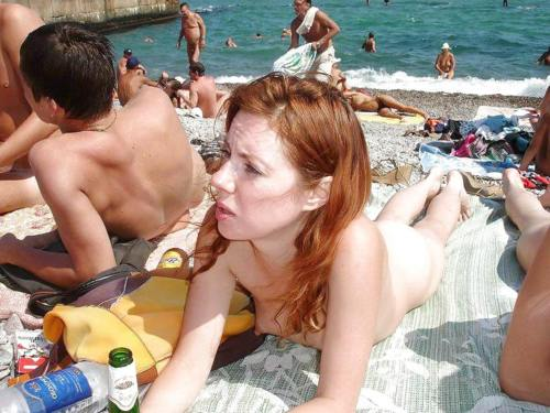 Redhead tanning on a nudist beach