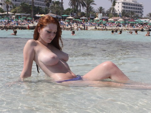Topless redhead cooling in the sea