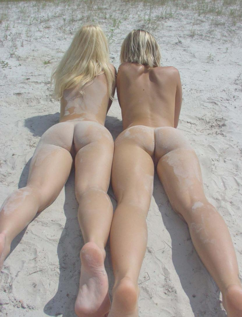 Two blondes showing their sand covered asses