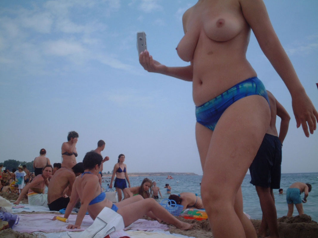 Topless babe proudly walk on the beach