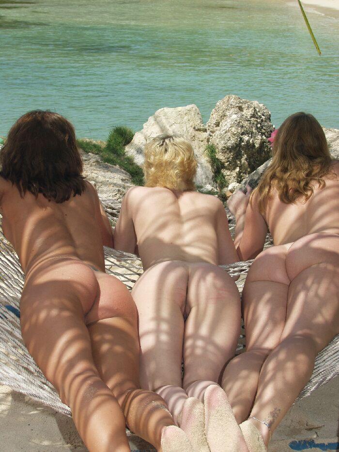 Three women tanning naked in a hammock