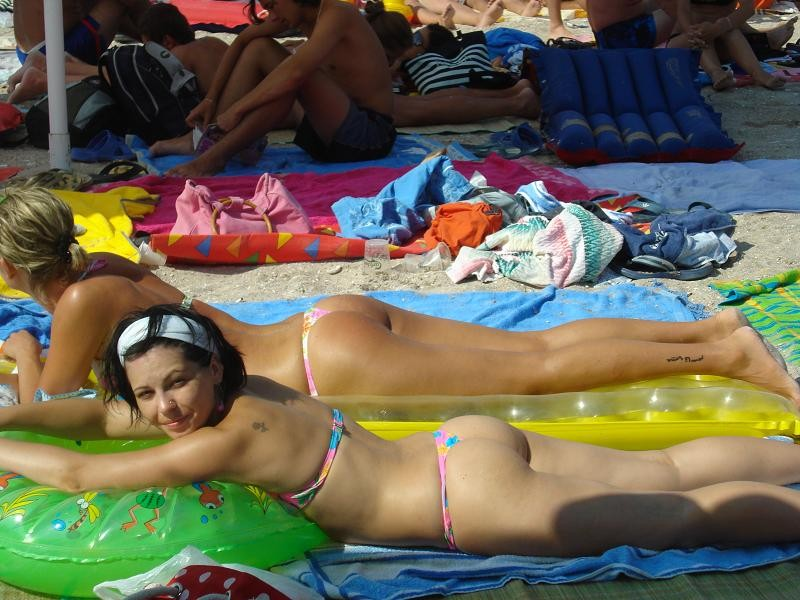 Hot beach girls tanning at the burning sun