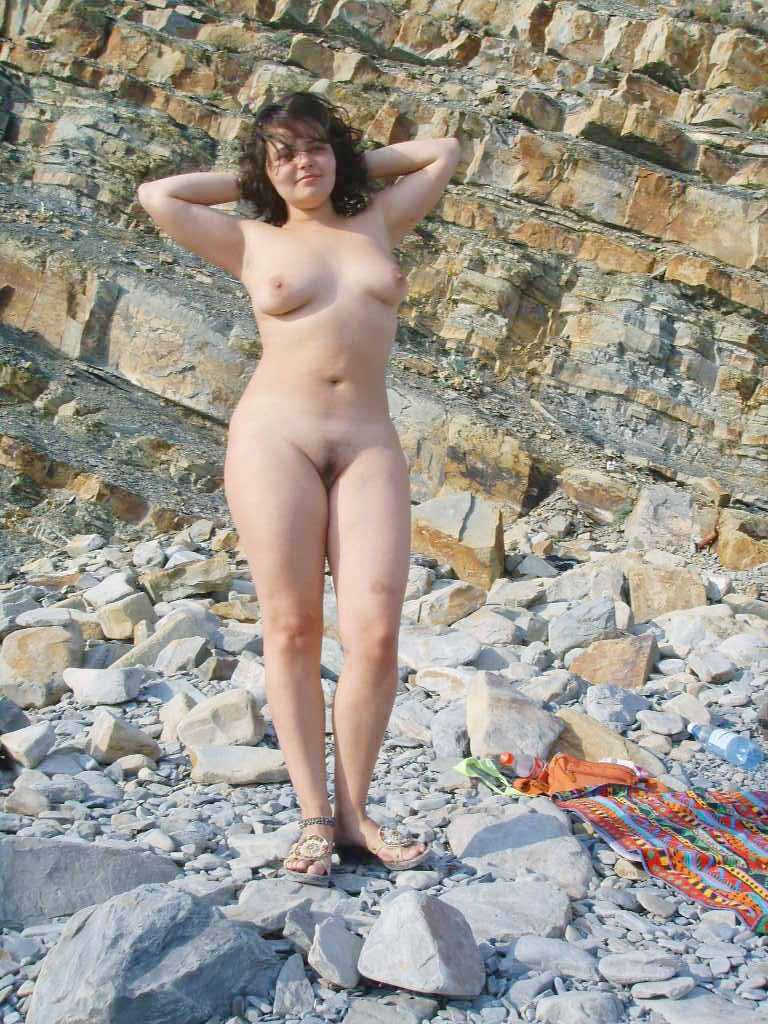 Voluptuous nude girlfriend shows her body on a rocky beach