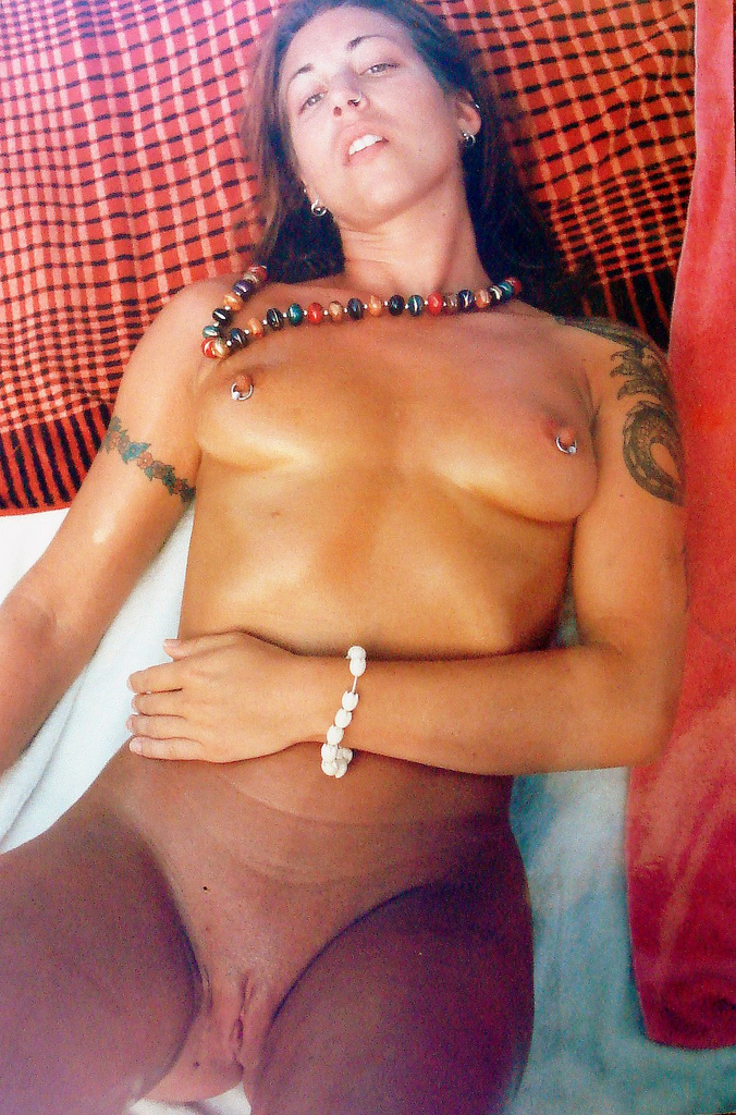 Hot tattooed babe laying on a blanket and tanning