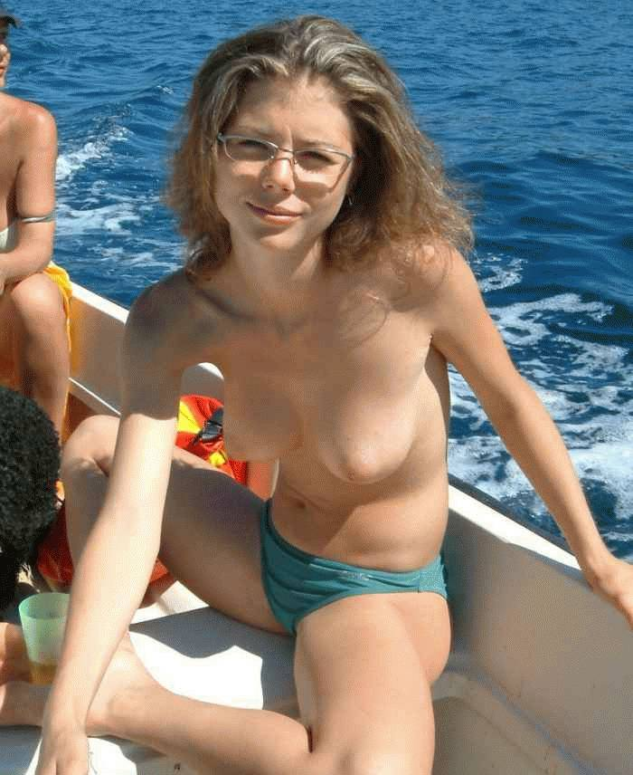 Nerdy chick topless on a boat