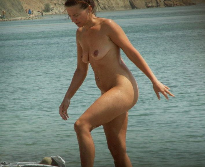 Nude lady exit from water and looks wonderful