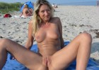 Blond naughty girl wide open legs and shaved pussy reveal on warm nude beach tanning at sun