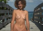 Curly brunette naked babe stand in a sexy position on a dockyard from far away exotic island