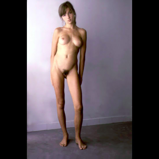 Lascivious babe with furry snatch and round firm pillows standing at the wall