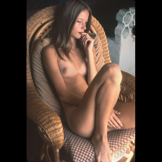 Thinking babe naked on the armchair muse to an artist