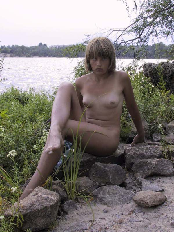 Awesome cute girl caught by voyeur on his camera showing some tiny tits and laying naked on a rocky shore
