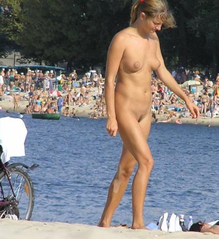 Crowded beach surprise a nudist girl on the sandy warm shore exposing her naked body