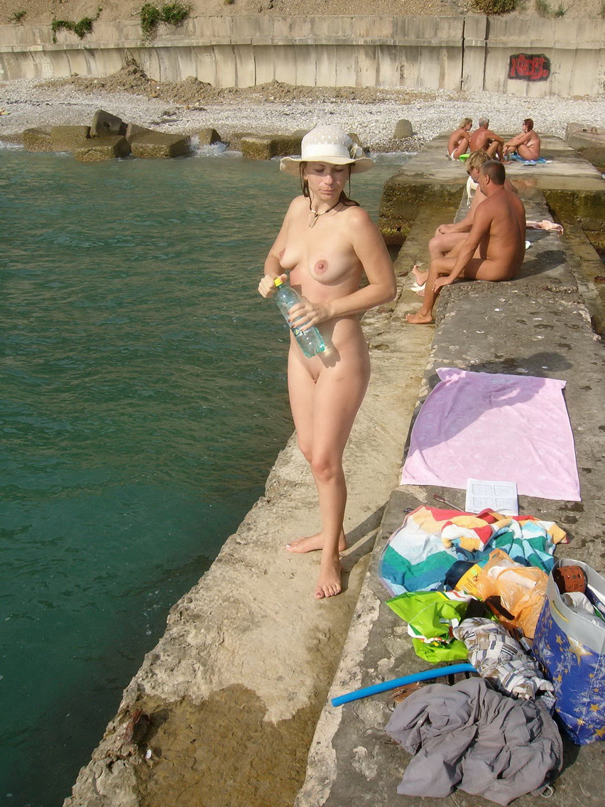Naturist young woman nude with cute hooters on a rocky beach caught by a professional photographer