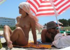 Nudist couple on the sunny beach caught while girlfriend expose her boobies