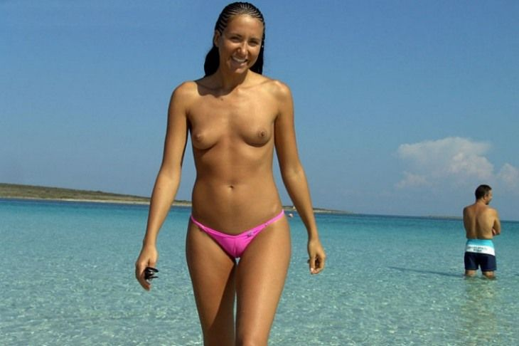 Pink thongs babe with sweet tiny boobies reveal her exciting cameltoe while takes a picture in the water of blue lagoon