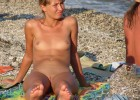 Young nude girl with shaved muff and sweet tiny boobies lays on the beach at nudist camp