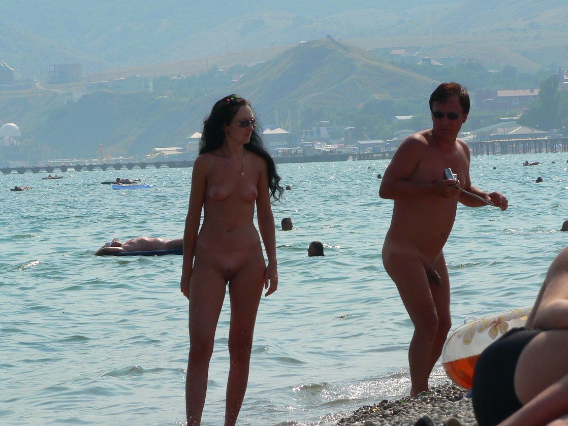 Young nudist couple at sunny beach while tanning wearing sunglasses