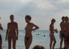 Couple of cute topless girls expose their beauty on sea shore