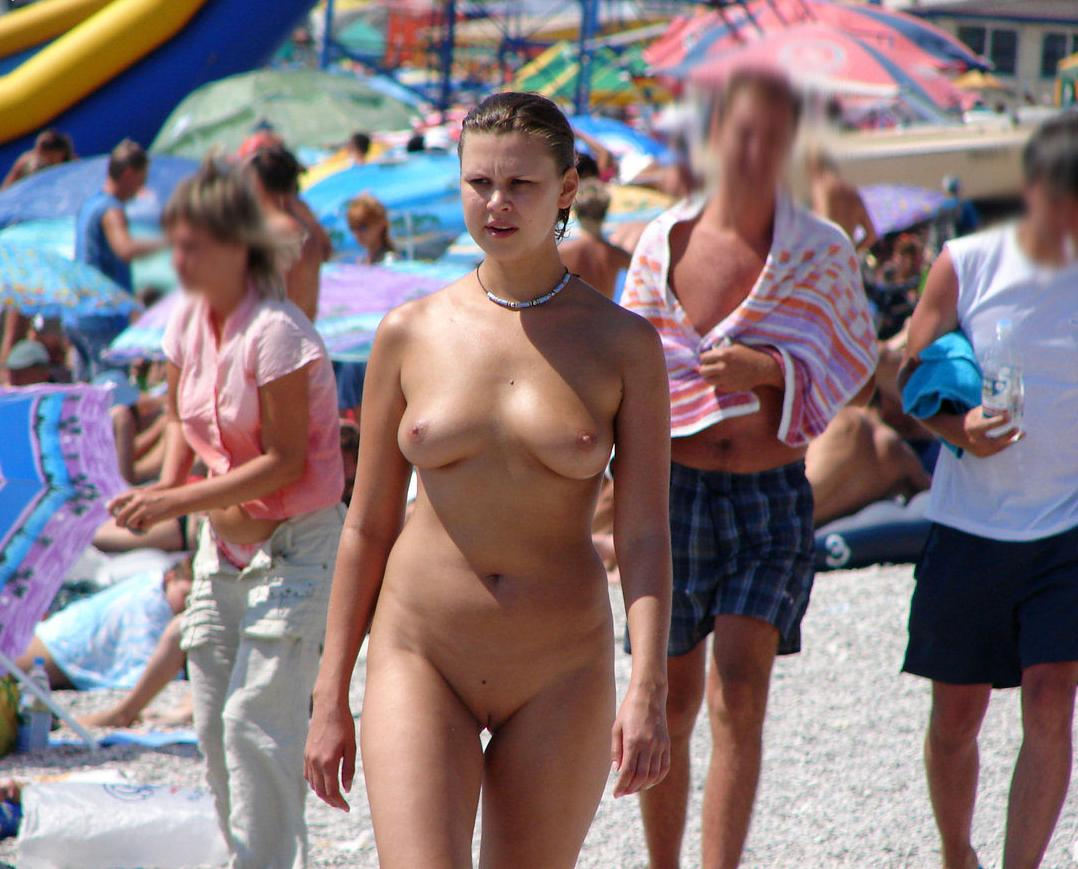 Blond babe with golden skin walking naked on the beach