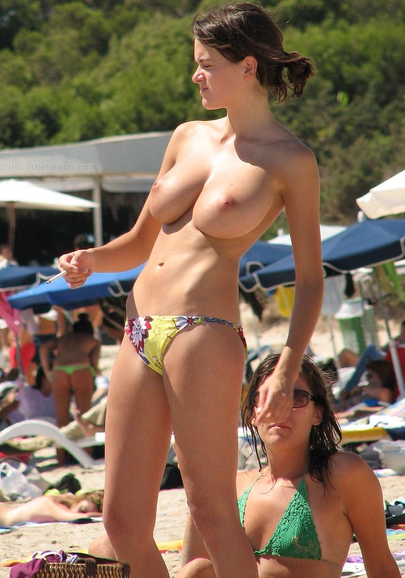 Voluptuous babe with no bra wearing only cute tiny bikini