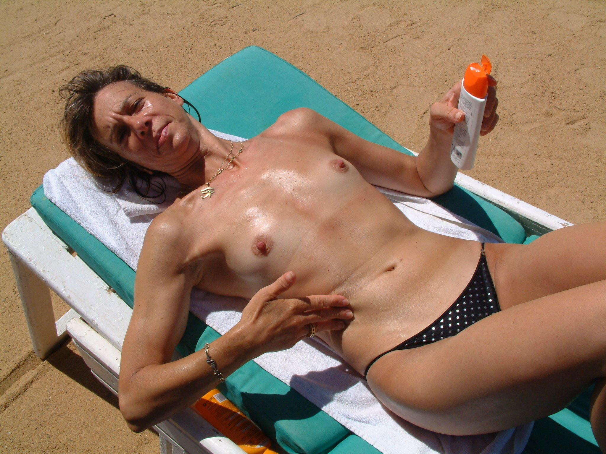 Naughty cougar asking photographer to apply sunscreen on her naked body