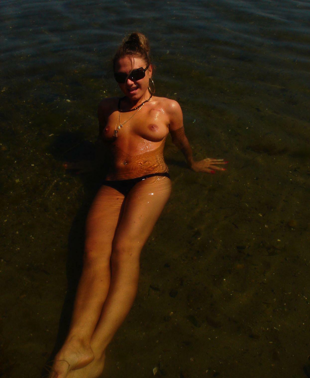 Semi nude girl goofs around the lake