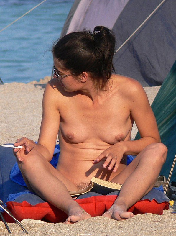 Smoking hot young nudist gets pussy covered from view with a book